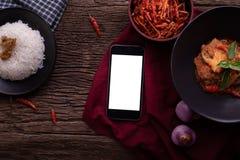 Köksbord med den tomma skärmen på den smarta telefonen, minnestavlan, mobiltelefonen och torkad röd grisköttkokosnötcurry royaltyfri bild