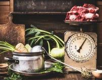 Köksbord med matlagningkrukan, slev, grönsaker och gammal weigher med rått kött, förberedelse av soppa, buljong eller ragu, främr fotografering för bildbyråer