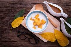 Köksbord med organisk yoturt med skivad mango- och fruktfruktsaft arkivbild