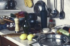 Köksgeråd, flaskor, grönsaker och smaktillsatser på kitcen royaltyfri foto