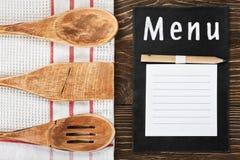 Köksgeråd och en notepad som skriver menyn Royaltyfria Bilder