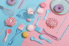 Köksgeråd och hjälpmedel, bakelser och sötsaker på en rosa och blå bakgrund Top beskådar kopiera avstånd royaltyfri foto