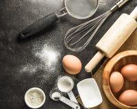 Köksgeråd och stekheta ingredienser: ägg och mjöl på svart bakgrund Arkivfoton