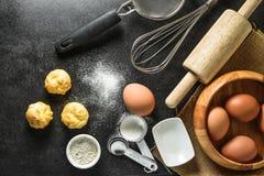 Köksgeråd och stekheta ingredienser: ägg och mjöl på svart bakgrund Fotografering för Bildbyråer