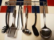 Köksgeråd som hänger på en kulör tegelplattavägg Fotografering för Bildbyråer