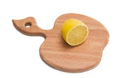Kökskärbräda med den halva citronen Royaltyfri Bild