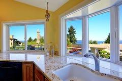 Köksskåp med granitblast och härlig fönstersikt Arkivbilder
