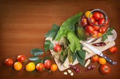 Kökstilleben av objekt som lagar mat inlagda tomater Arkivfoto