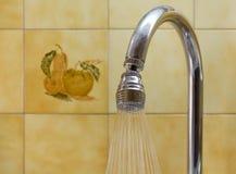 Kökvattenkran mot en belagd med tegel vägg Royaltyfri Foto