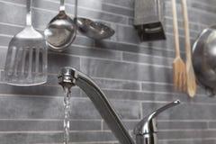 Kökvattenkranen bevattnar royaltyfria foton