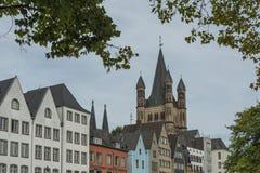 KÖLN, DEUTSCHLAND - 11. SEPTEMBER 2016: Bunte Häuser in der bayerischen Art und im romanischen katholische Kirche ` verdienen ` S Lizenzfreies Stockbild