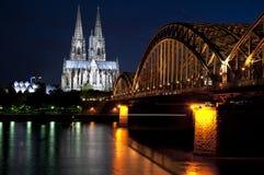 Köln-Kathedrale mit Eisenbahnbrücke nachts Stockbilder