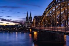 Köln-Kathedrale und Zug-Brücke nachts Stockbilder