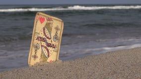 König der Spielkarte der Herzen fest im Sand durch das Meer stock footage