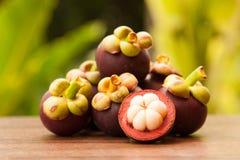 Königin der Frucht, der Mangostanfrüchte und des Querschnitts, welche die weiße Haut über dem Holztisch im Garten zeigen Stockbild