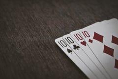 Königliche Spaten des Spielkartekasinoblinkens Vier zehn auf einer Holztischnahaufnahme Abstraktionshintergrund und Spielen Stockbild
