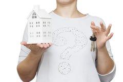 köp det nya begreppshuset Närbild av flickainnehavmodellen av huset i en hand och tangenter i annan hand Arkivfoto