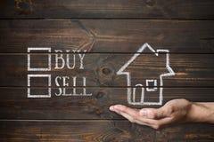 Köp eller sälj huset som är skriftligt på träbräden Royaltyfria Bilder