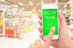 KÖP för kvinnahandklick NU på mobil med suddighetssupermarketbackgro Arkivfoto