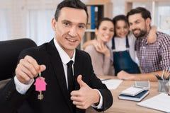 Köpa en egenskap Den glade fastighetsmäklaren gjorde ett fördelaktigt erbjudande för att köpa huset för ung familj arkivfoto