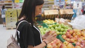 Köpandeäpplen för ung kvinna i supermarket stock video