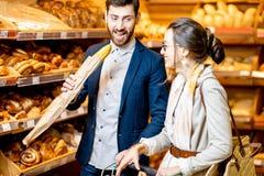 Köpande bageri för par i supermarket fotografering för bildbyråer