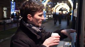 Köpande för ung man i coffeeshoppapperskopp kaffe på stadsgatan på natten lager videofilmer