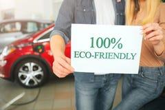 Köpande första elbil för ung familj i visningslokalen Eco bil Närbild av händer som rymmer papper med ordEco-vänskapsmatch arkivfoto