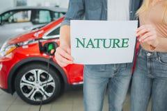Köpande första elbil för ung familj i visningslokalen Grön bil Närbild av händer som rymmer på papper med ordnaturen fotografering för bildbyråer