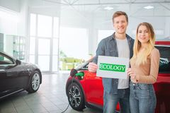 Köpande första elbil för ung familj i visningslokalen Le attraktiva par som rymmer papper med grön ordekologi royaltyfria foton