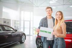Köpande första elbil för ung familj i visningslokalen Le attraktiva par som rymmer papper med ordelbilen arkivbild