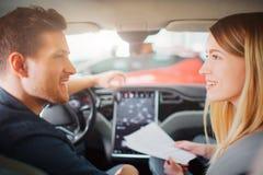 Köpande första elbil för unga par i visningslokalen Attraktiv familj som talar om bilköp i kabinen av arkivfoto