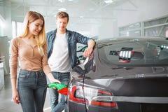 Köpande första elbil för unga par i visningslokalen Kvinna som laddar den ekologiska hybrid- bilen med tillförselen för maktkabel royaltyfri fotografi