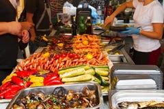 Köpande foods för folk på matstallen på internationell festivalhändelse för öppet kök av gatamat arkivfoton