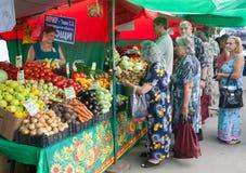 Köpande grönsaker för folk i grönsakmässa Fotografering för Bildbyråer