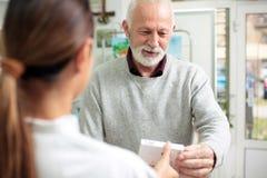 Köpande läkarbehandlingar för hög manlig patient i apotek arkivbilder
