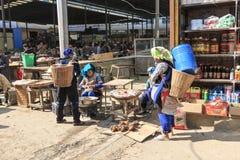 Köpande material för Hani folk i Shengcun den lokala marknaden i YuanYang Hani är en av de 56 minoriteterna i Kina och är infödin Arkivbilder