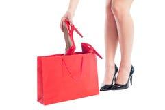 Köpande nya röda skor för elegant kvinna på försäljning Arkivbild