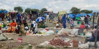 Köpande produkter för folk på marknaden på marschen i africa Arkivbild