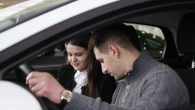 Köpare som har konversation med bilsäljaren under kontroll av bilen arkivfilmer