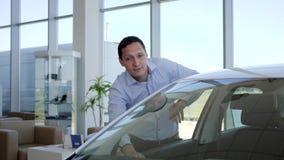 Köparebilshower tummar upp, den auto affären, bilförsäljningen, teknologi och folkbegreppet - lycklig manlig klient i auto show e lager videofilmer