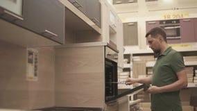 Köparen kontrollerar utställningsföremålet av ugnen i kök i ett möblemanglager arkivfilmer