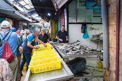 Köparen väljer upp fisken från magasinet i fiskmarknaden på marknaden i den gamla staden av tunnlandet i Israel Royaltyfri Fotografi