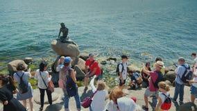 Köpenhamn Danmark, Juli 2018: En folkmassa av turister fotograferas nära den berömda statyn av den lilla sjöjungfrun in stock video