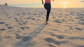 Kör den härliga kvinnan för sunda unga sportar längs sanden, på stranden, i sommar, in mot solen, på soluppgången stock video