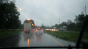 Kör på vägen i regnet med suddig bakgrund och ljus bokeh på aftonen stock video