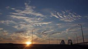 Kör till och med Brigen under konstruktion med dramatiska moln och inställningssolen Solnedgång lager videofilmer