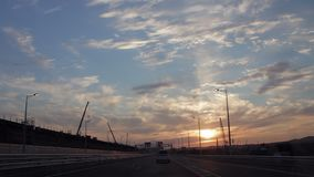 Kör till och med Brigen under konstruktion med dramatiska moln och inställningssolen Solnedgång arkivfilmer