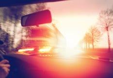 Köra en bil i morgonen mot soluppgång som passerar en lastbil arkivbild
