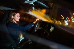 Köra en bil på den nätta natten -, ung kvinna som kör hennes bil royaltyfri fotografi